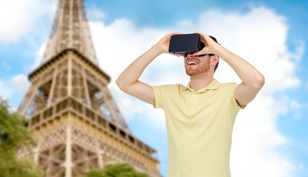 mediated: 3d technology, virtual reality, travel, entertainment and people concept - happy young man with virtual reality headset or 3d glasses over paris eiffel tower background Stock Photo