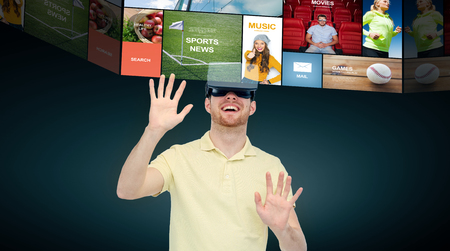 entertainment background: 3d technology, virtual reality, cyberspace, entertainment and people concept - happy young man with virtual reality headset or 3d glasses networking over black background Stock Photo