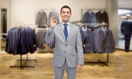 Geschäft, Leute, Menswear, Verkauf und Kleidungskonzept - glücklicher lächelnder Geschäftsmann in der Klage über dem Bekleidungsgeschäfthintergrund, der okayhandzeichen zeigt Standard-Bild