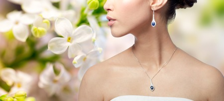 asian natural: beauty, jewelry, wedding accessories, people and luxury concept - close up of beautiful asian woman or bride with earring and pendant over natural spring lilac blossom background