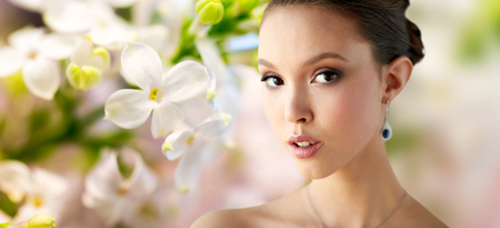 asian natural: beauty, people, make up and luxury concept - close up of beautiful asian woman or bride with earring over natural spring lilac blossom background Stock Photo