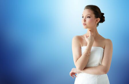 bride bangle: beauty, jewelry, wedding accessories, people and luxury concept - beautiful asian woman in white dress or bride with golden bracelet over blue background
