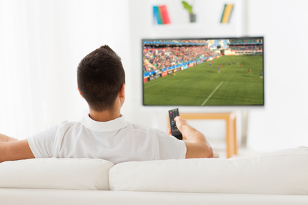 leisure, technology, sport, entertainment and people concept - man with remote control watching football or soccer game on tv at home Stock Photo