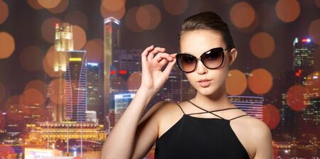 eyewear fashion: accessories, eyewear, fashion, people and luxury concept - beautiful young woman in elegant black sunglasses over night city lights background