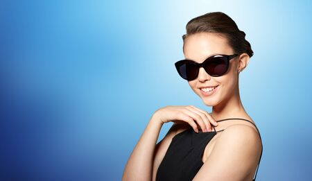 eyewear fashion: accessories, eyewear, fashion, people and luxury concept - beautiful young woman in elegant black sunglasses over blue background