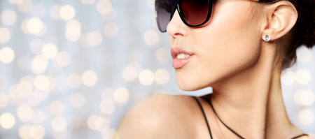 background summer: accessories, eyewear, fashion, people and luxury concept - close up of beautiful young woman in elegant black sunglasses over holidays lights background