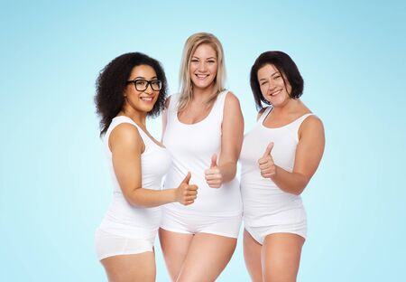 posing  agree: gesture, friendship, beauty, body positive and people concept - group of happy plus size women in white underwear showing thumbs up over blue background Stock Photo