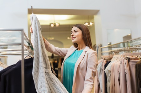 woman closet: sale, shopping, fashion, style and people concept - happy young woman choosing clothes in mall or clothing store Stock Photo