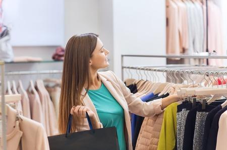 Verkauf, Mode, Konsum und Menschen Konzept - glückliche junge Frau mit Einkaufstüten Kleidung in der Mall oder Bekleidungsgeschäft Wahl