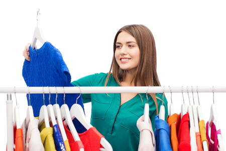 woman clothes: clothing, shopping, fashion, style and people concept - happy woman choosing clothes at home wardrobe