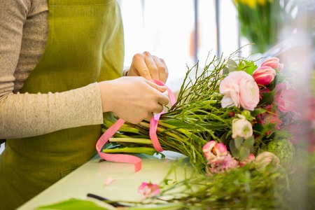 people, business, sale and floristry concept - close up of florist woman making bunch at flower shop Фото со стока