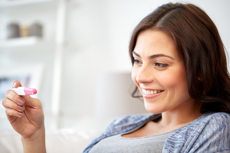 wait: pregnancy, fertility, maternity and people concept - happy smiling woman looking at pregnancy test at home