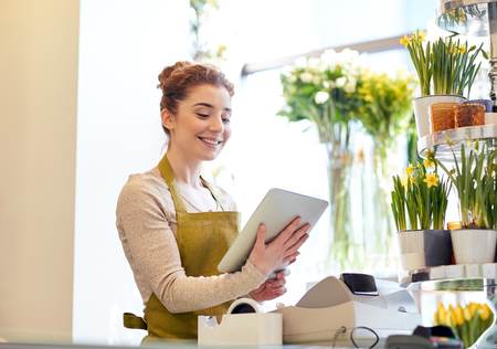 floristry: people, business, technology, sale and floristry and concept - happy smiling florist woman with tablet pc computer at flower shop