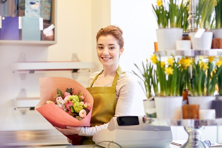 floristry: people, business, sale and floristry concept - happy smiling florist woman holding bunch of flowers wrapped into paper at flower shop Stock Photo