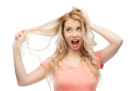 strand of hair: hair care, hairstyle and people concept - young woman or teenage girl holding strand of her hair Stock Photo