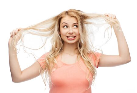 damaged: hair care, hairstyle and people concept - young woman or teenage girl holding strand of her hair Stock Photo