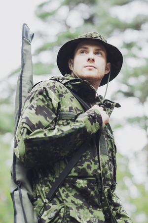 infantryman: hunting, war, army and people concept - young soldier, ranger or hunter with gun walking in forest