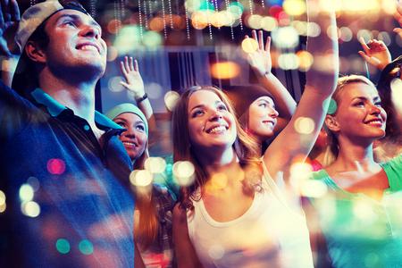 fiesta, fiestas, eventos de música, vida nocturna y la gente concepto - grupo de amigos felices en el concierto de hip-hop en club nocturno
