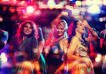 party, holidays, celebration, nightlife and people concept - happy friends dancing in club with holidays lights Stock Photo