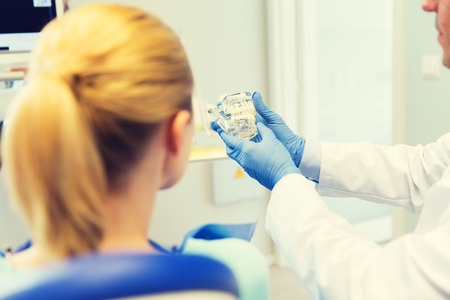 stomatologist: people, medicine, stomatology and health care concept - happy male dentist showing jaw and teeth layout to patient woman at dental clinic office Stock Photo
