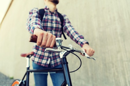 travel gear: people, travel, tourism, leisure and lifestyle - close up of young hipster man with fixed gear bike and backpack on city street