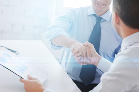 businesss y la oficina concepto - dos hombres de negocios dándose la mano en la oficina