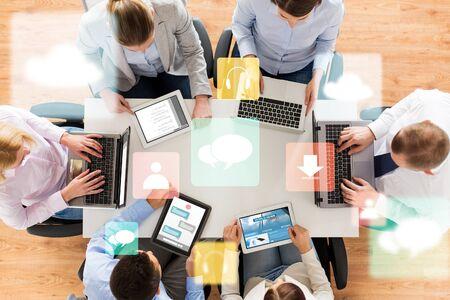 affaires, les gens, les médias et concept technologique - close up de l'équipe créative avec les ordinateurs portables et ordinateurs tablettes pc assis à une table dans le bureau Banque d'images