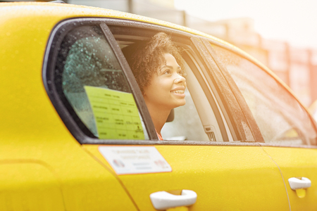 looking out: business trip, transportation and people concept - young smiling african american woman driving in taxi at city street