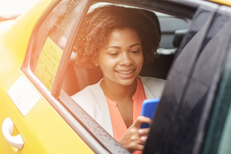 going: business trip, transportation, travel, gesture and people concept - young smiling african american woman texing on smartphone in taxi at city street