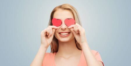 girl with gray eyes: love, romance, valentines day and people concept - smiling young woman or teenage girl with red heart shapes on eyes over gray background