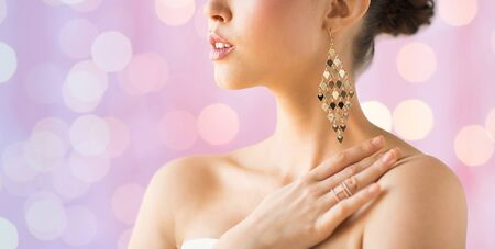 glamour luxury: glamour, beauty, jewelry and luxury concept - close up of beautiful woman with earrings over pink holidays lights background