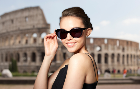 eyewear fashion: accessories, eyewear, fashion, people and luxury concept - beautiful young woman in elegant black sunglasses over coliseum background Stock Photo
