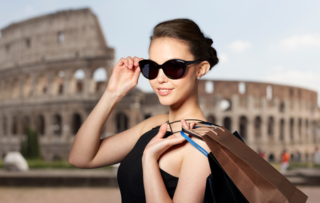 sale, tour, fashion, people and luxury concept - happy beautiful young woman in black sunglasses with shopping bags over coliseum background