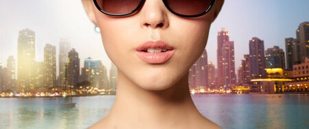eyewear fashion: accessories, eyewear, fashion, people and luxury concept - close up of beautiful young woman in elegant black sunglasses over dubai night city lights street background