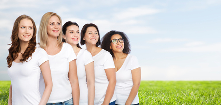natural backgrounds: friendship, diverse, body positive and people concept - group of happy different size women in white t-shirts over blue sky and grass background