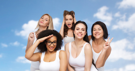 friendship, beauty, body positive and people concept - group of happy plus size women in white underwear having fun and making faces over blue sky and clouds background Stock Photo