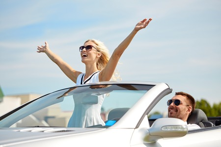 cabriolet: transport, leisure, road trip and people concept - happy man and woman driving in cabriolet car outdoors