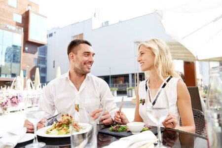 dinner date: love, date, people, holidays and relations concept - happy couple eating salad for dinner at cafe or restaurant terrace