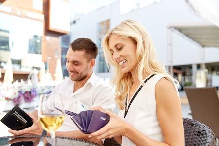 pagando: fecha, las personas, el pago y las finanzas concepto - pareja feliz con vasos de vino billetera y pagar la cuenta en un restaurante