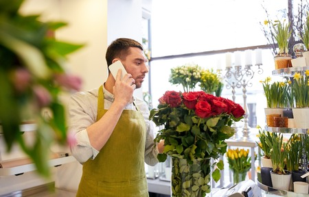 people, sale, retail, business and floristry concept - florist man with red roses calling on smartphone at flower shop counter Stock Photo