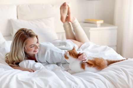 kitties: pets, morning, comfort, rest and people concept - happy young woman with cat in bed at home