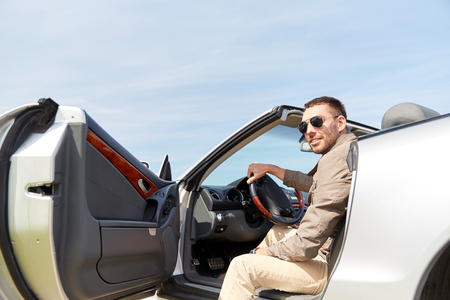 open car door: road trip, travel, transport, leisure and people concept - happy man opening door of cabriolet car outdoors Stock Photo