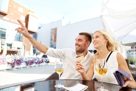bill payment: date, people, payment and finances concept - happy couple with wallet, credit card and wine glasses calling waiter for bill payment at restaurant Stock Photo