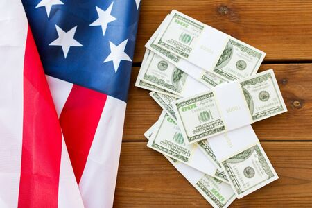 nationalism: budget, finance and nationalism concept - close up of american flag and dollar cash money packets