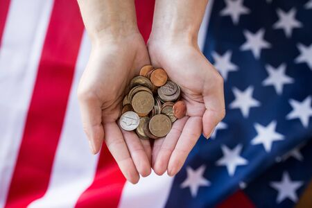 money crisis: finances, money, crisis, investment and state budget concept - ose up of hands with coins over american flag Stock Photo