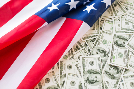 united: budget, finance and nationalism concept - close up of american flag and dollar cash money