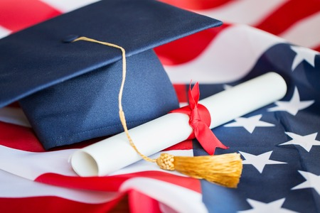 education, graduation, patriotism and nationalism concept - close up of bachelor hat and diploma on american flag Stock Photo