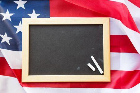 independencia: la educación, la elección, el patriotismo y el nacionalismo concepto - cerca de la pizarra de la escuela en blanco y tiza en la bandera americana