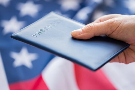 nationalism: citizenship, patriotism and nationalism concept - close up of hand with american passport