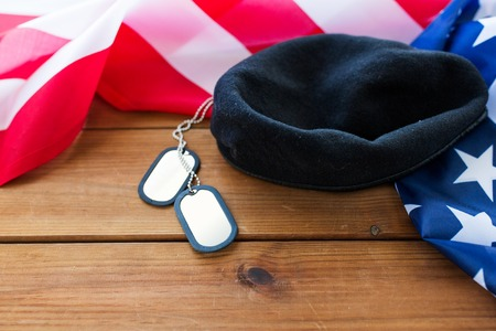 conscription: military forces, service, patriotism and nationalism concept - close up of american flag, soldiers badges and paratrooper hat on wood Stock Photo